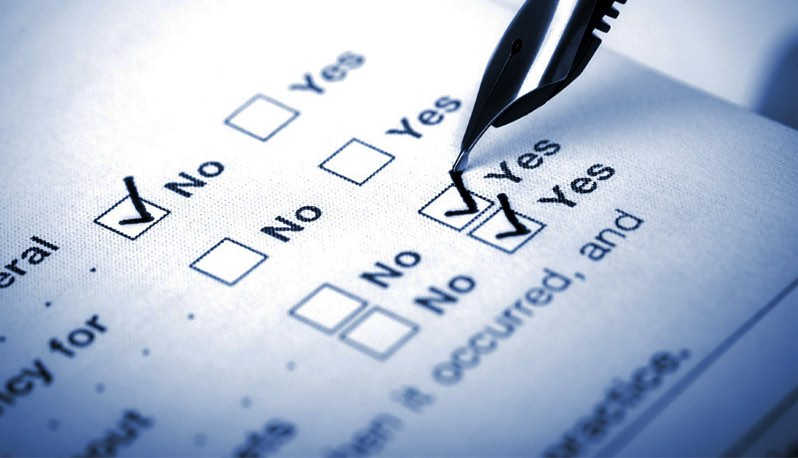 Pen filling out checkboxes on a piece of paper